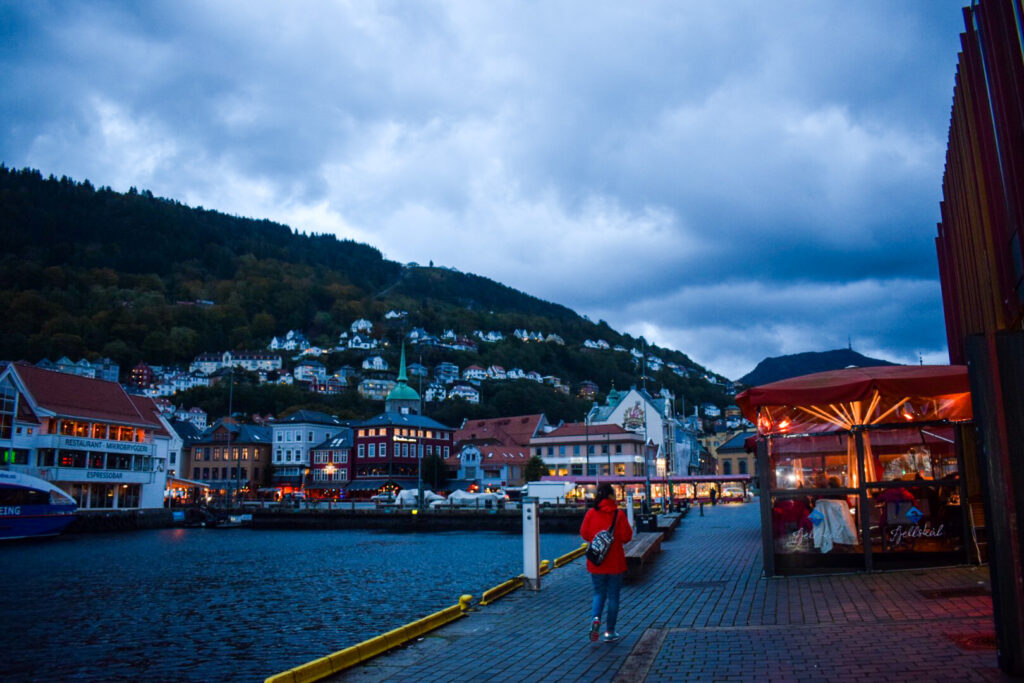 A girl in a red coat walks through the  harbour by the Fjord in Bergen.