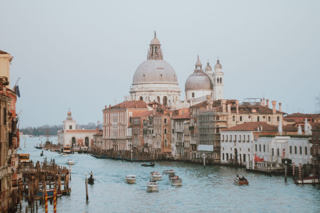 Stock photo of Venice with several boats flowing through a canal by Anastasiya Lobanovskaya from Pexels. Venice is an amazing day trip from Milan.