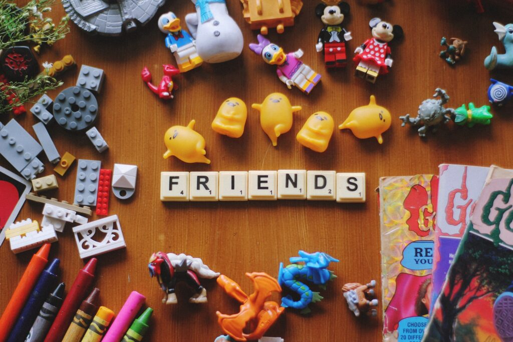 A wooden table covered in children's toys and scrabble pieces spelling out the word 'friends'.