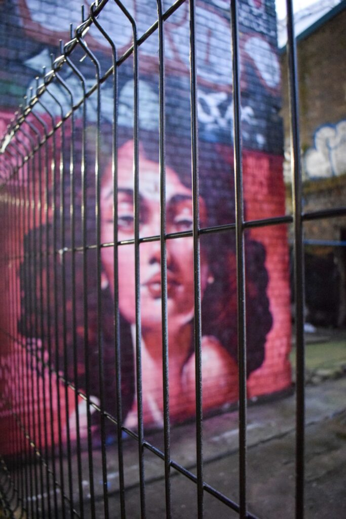 A red toned street art portrait of a woman through bars in Digbeth, Birmingham by Phill Blake.