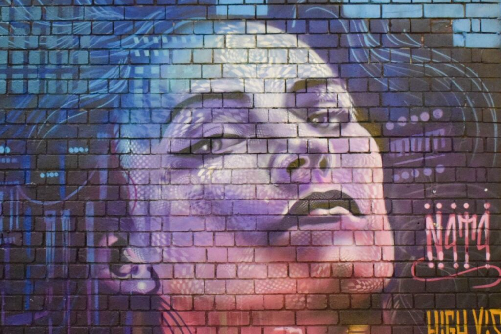 A mural of a woman's face with colourful lighting and patterns by street artist N4T4 in Digbeth, Birmingham.