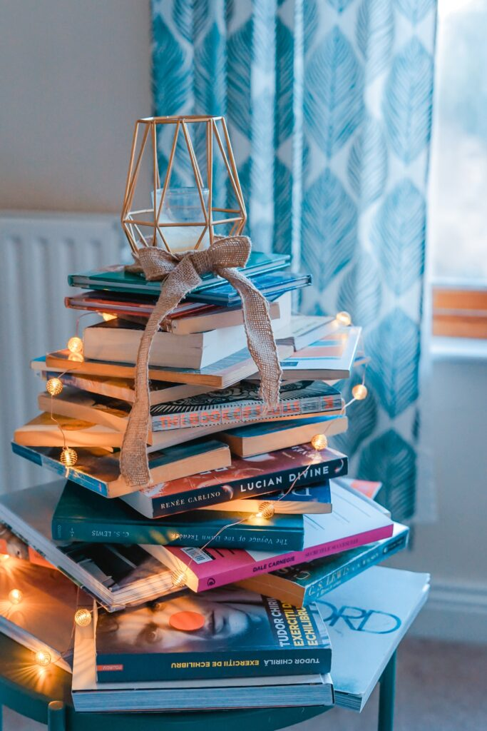 A pile of books covered in fairy lights and topped with a candle. An online book club is a great idea for connecting with friends and family when you're far apart.