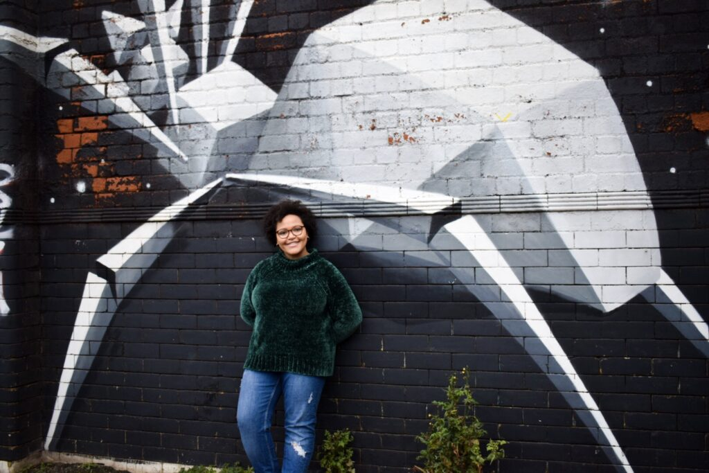 Imani posing with a street art mural of a geometric spider by artist Anatomix in Digbeth, Birmingham.