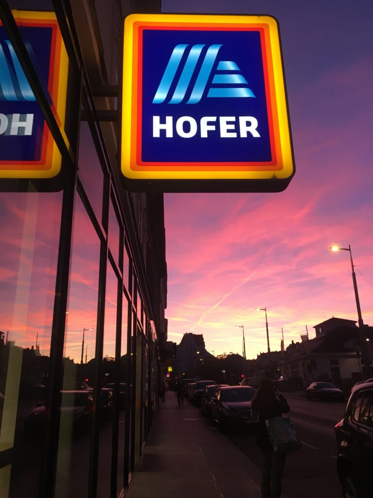 A sunset in Naschmarkt, Vienna, reflected in the window of a Hofer/Aldi store.