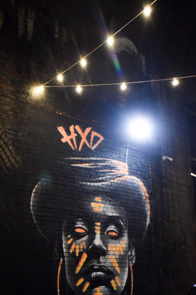 A street art painting in Digbeth, Birmingham, of a voodoo queen with neon accents by artist Justin Sola.