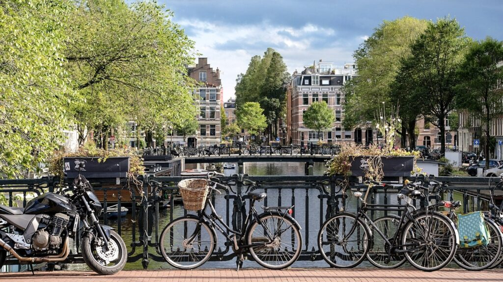 Bikes leaning against a bridge railing over a canal in Amsterdam. Use your bike to explore Amsterdam Noord in the evening.