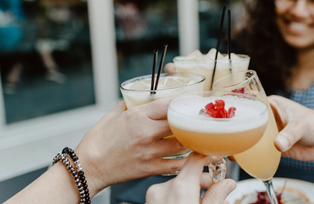 A group of girls clinking cocktail glasses together.
