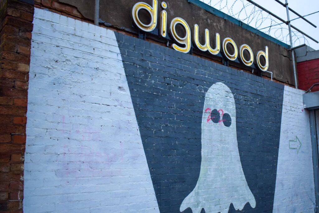 A street art painting of a ghost with 2020 written over the eyes under a digwood sign in Digbeth, Birmingham.