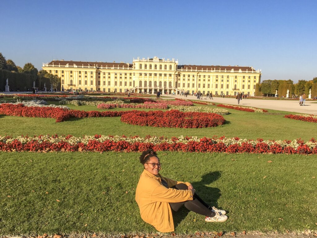 Imani sitting on the lawns on Schönbrunn Palace in Vienna. Schönbrunn Palace is a great thing to do if you only have 72 hours in Vienna.