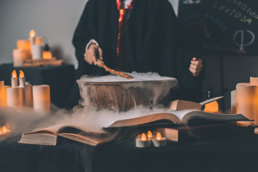 A person in a black robe and gryffindor style tie with a wand and cauldron, performing a spell.