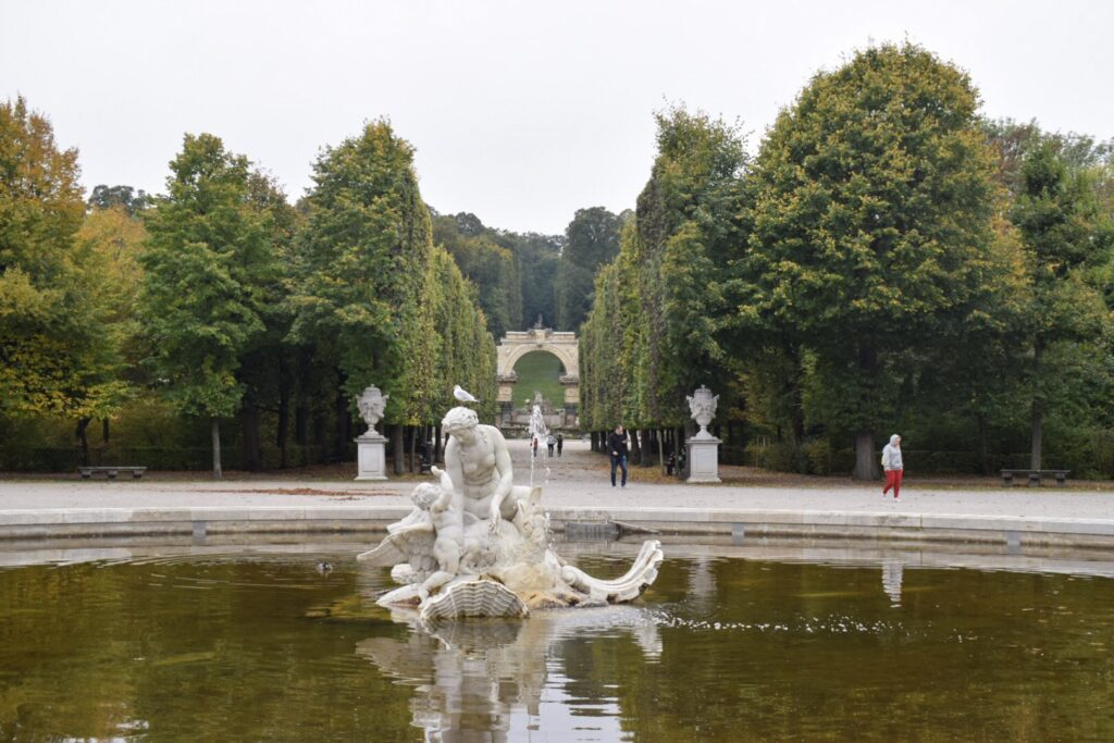 A statue in a fountain and tree lined walkways at Schönbrunn Palace gardens in Vienna.