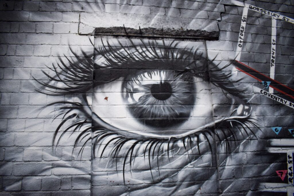 A close up street art painting of an eye featuring a map of the adigbeth Dozen in Birmingham.