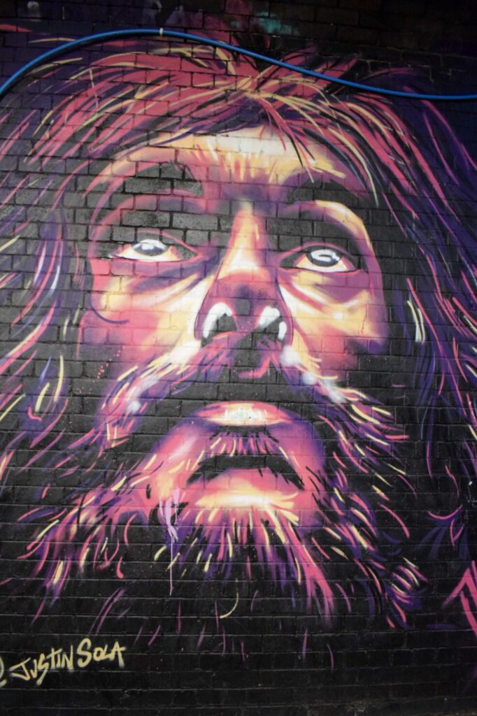 A street art painting of a hairy, bearded male figure by Justin Sola under the floodgate Street arches in Digbeth, Birmingham.