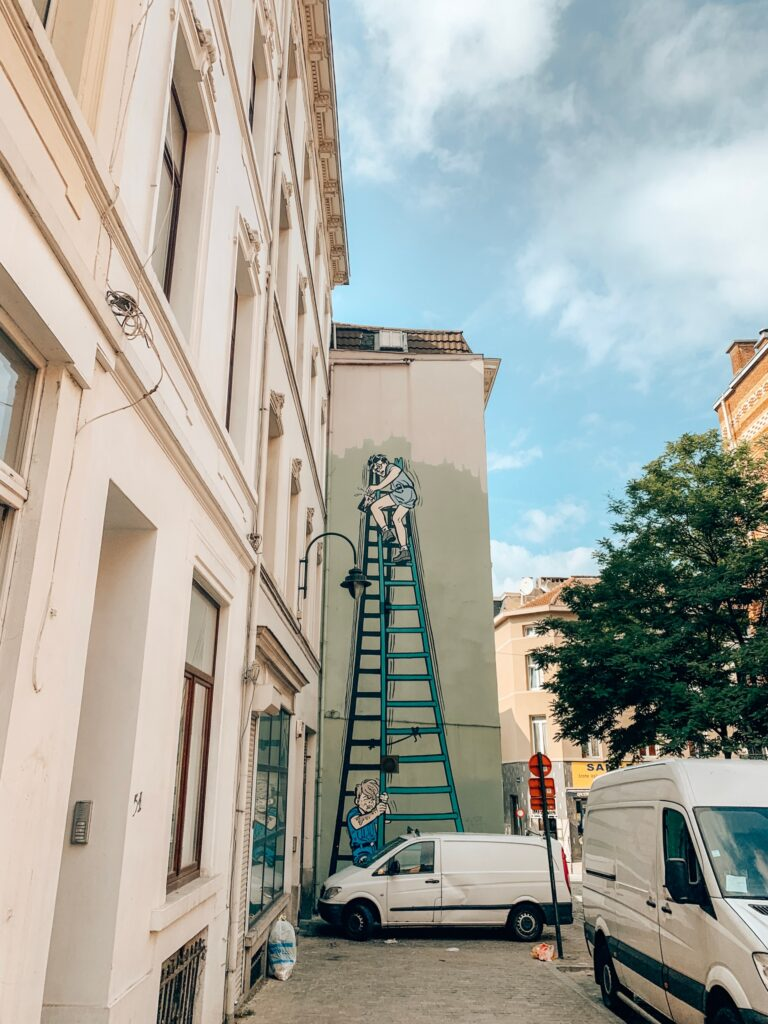 A mural of the Beaver Patrol by MiTacq and Jean-Mi he'll Charlier of two scouts painting a wall on the Brussels Comic Book Route.