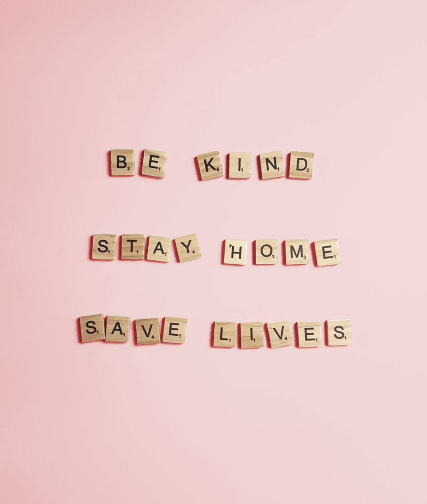 Scrabble pieces on a pink background reading 'Be Kind, Stay Home, Save Lives'
