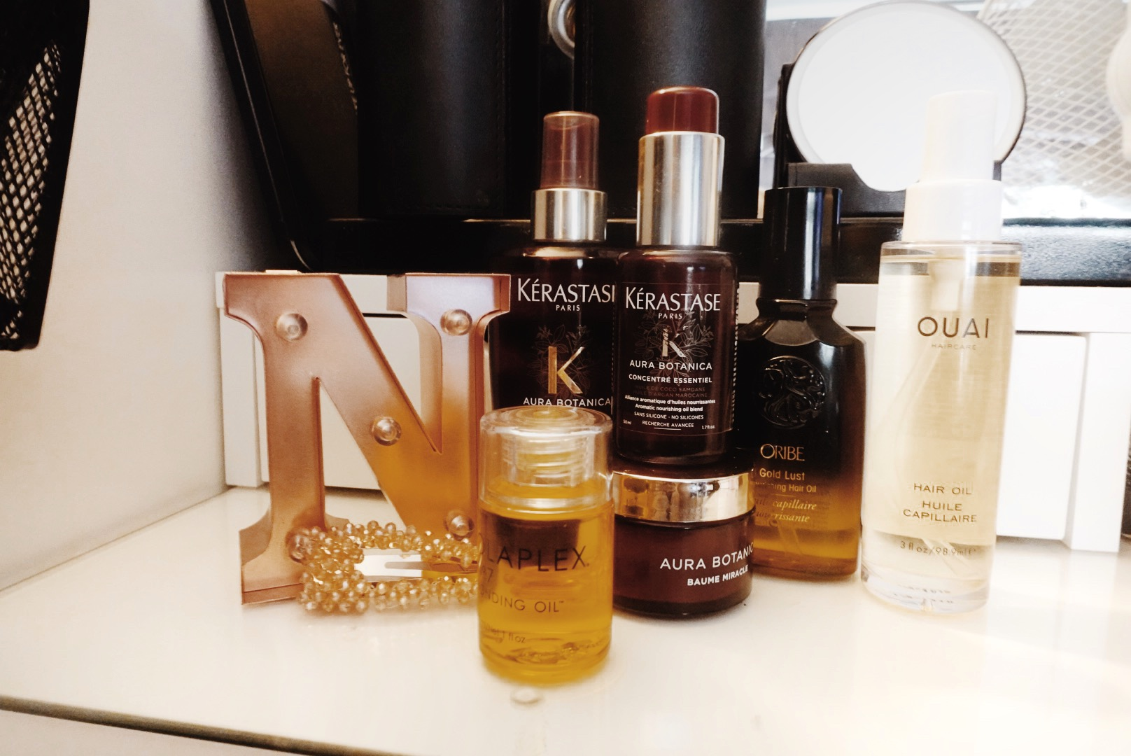 Bottles of various hair oils placed next to each other on the glass counter of a white vanity table. There's also a rose gold coloured letter N used as decor along with the bottles of hair oil mentioned in the blog post.