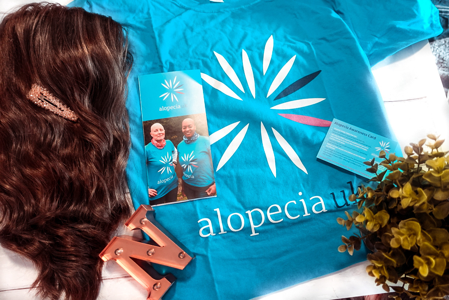 A flat flat of assorted items on a white table, the items include a bright blue t-shirt from Alopecia UK, a small rose gold letter N, a wig by Jon Renau called Heidi in a brunette colour and a small green house plant.