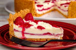 Cheesecake cu ciocolată albă și sos de zmeură