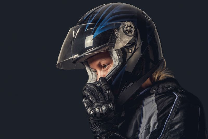 Female in motorcycle safety costume and black helmet.
