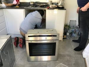 an electrician installing an oven