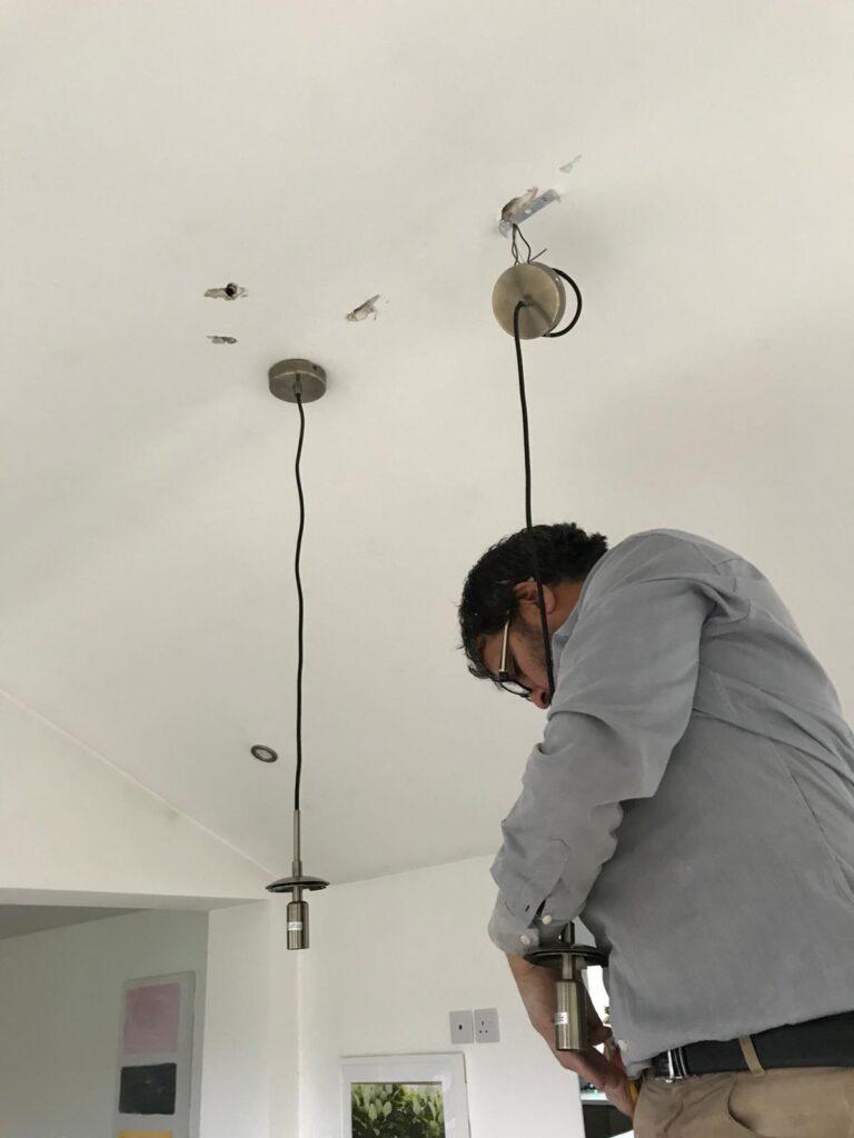 an electrician installing a chandelier