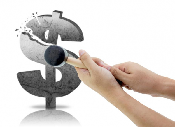 A person shattering a dollar sign with a gavel