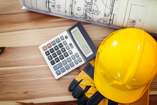 construction blueprints and calculator depicting cost estimation efforts