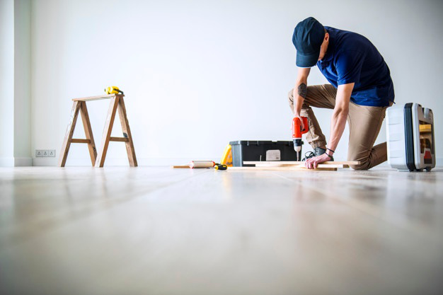 a person cutting and measuring floor planks