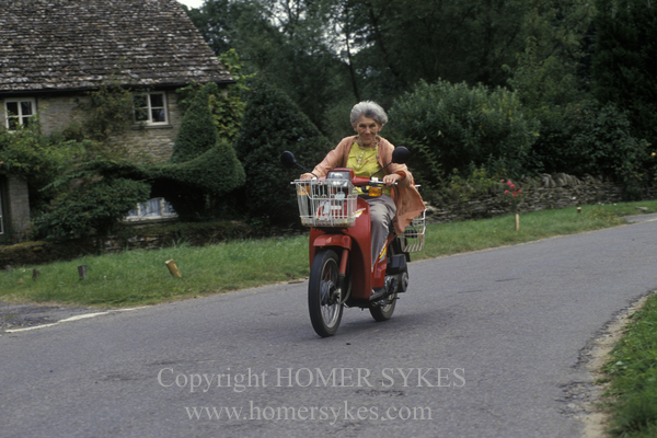 Eastleach Turville, Gloucestershire, England. Traditional village annual fete. An elderly member of the village community speeds about on her motor scooter.