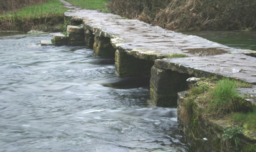 The Keble Bridge with a torrent flowing underneath - Eastleach