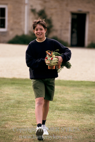 A YOUNG EDWARD ARKELL WITH HIS ENTRY FOR THE STRANGE VEGETABLE ANIMALS COMPETITION AT THE EASTLEACH VILLAGE FETE