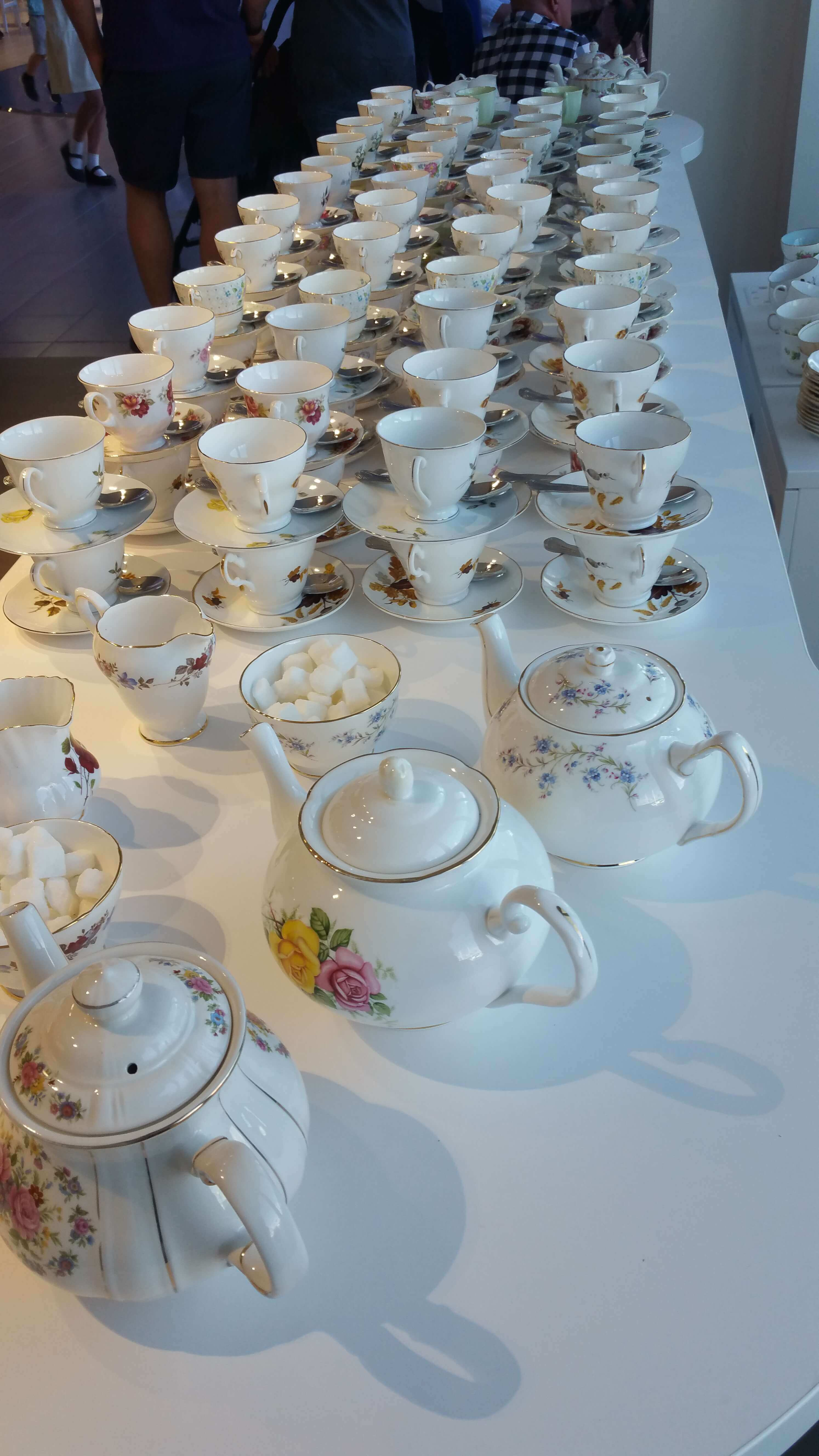 Photo shows vintage tea cups and tea pots lined up ready for tea to be served