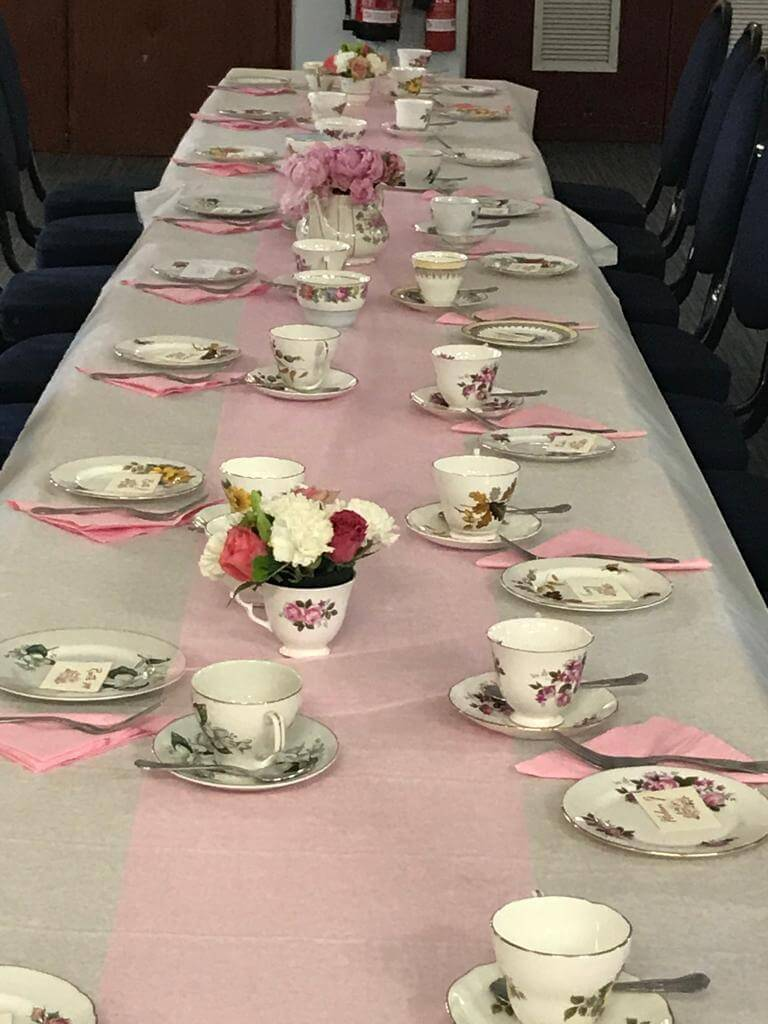 Photo shows a long table with vintage china ready for an Afternoon Tea Party