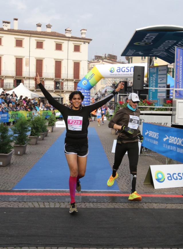 indian woman running through finish line