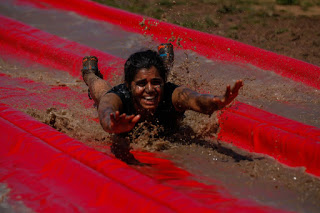 indian woman covered in mud down a slide