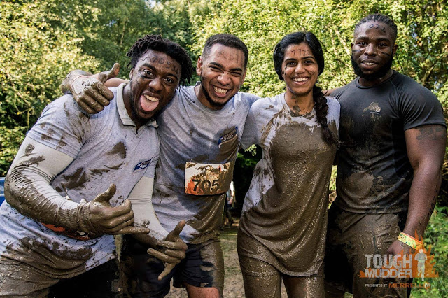 group of three black men and one indian woman covered in mud