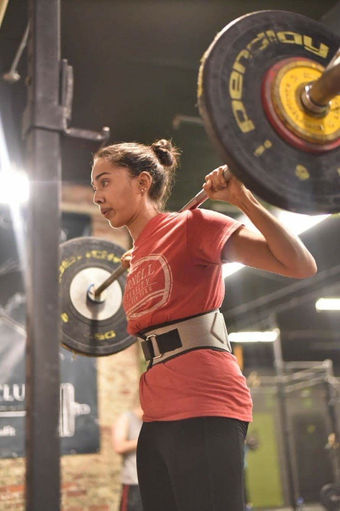 indian woman wearing a weightlifting belt, holding heavy barbell for a squat