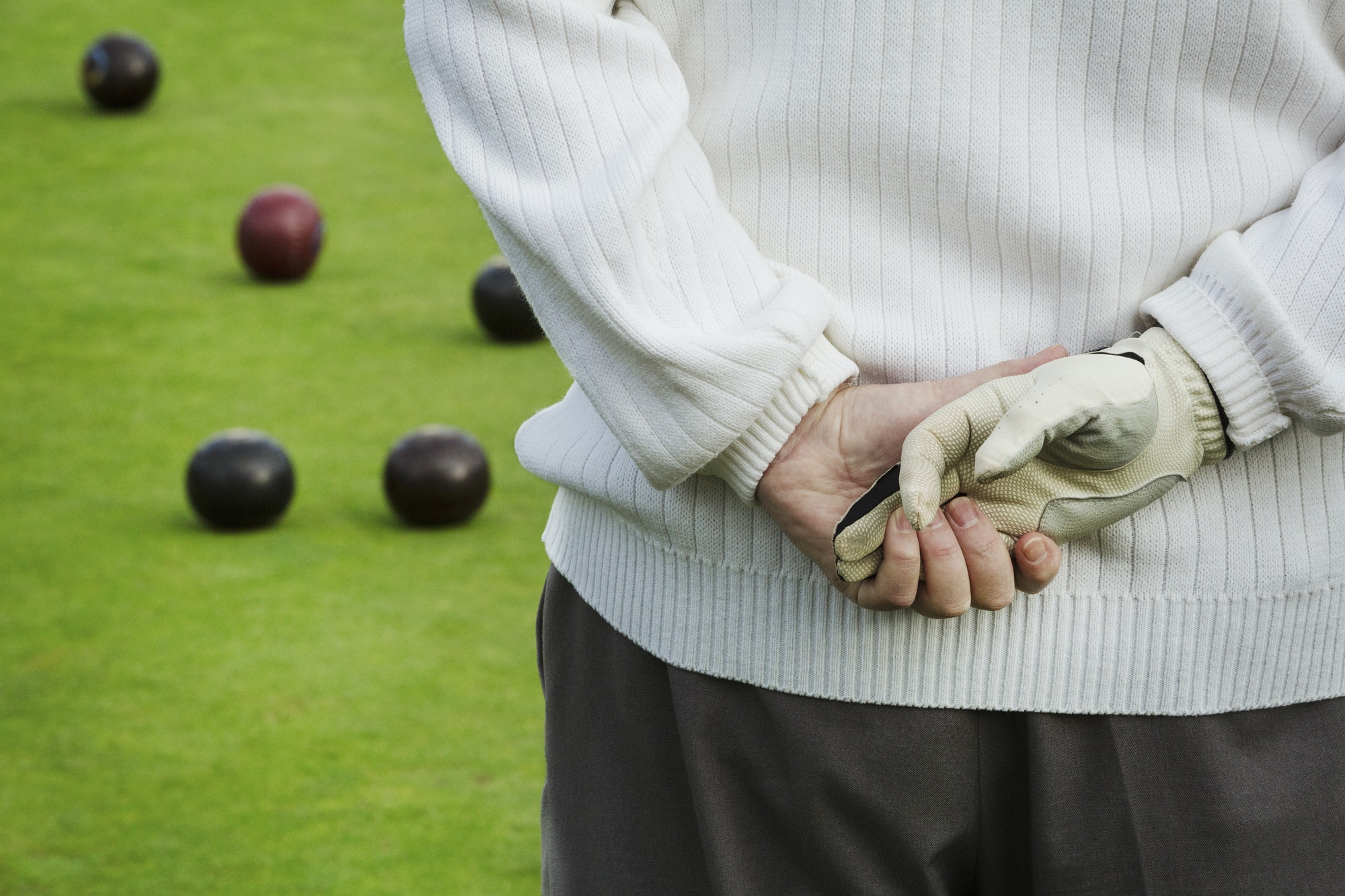Rear view, a man standing with his hands clasped behind him, one hand in a playing glove, at a lawn