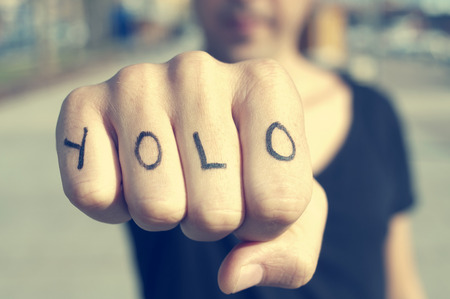 Close-up of a young man with the word YOLO, for You Only Live Once, tattooed in his hand