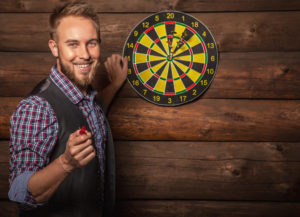 Portrait of young friendly man against old wooden wall with darts game