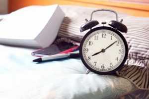 Alarm clock and writing material on the bed
