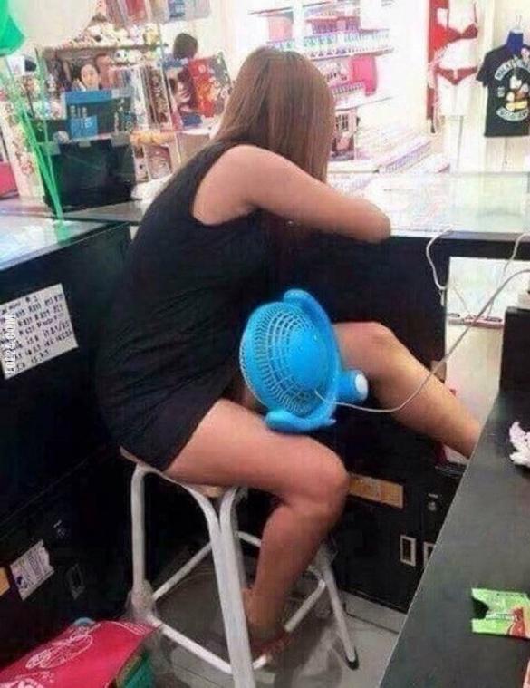 Смішне фото про спеку. В спеку дівчина продавчиня дує вентилятором собі під спідницю, щоб охолодити геніталії