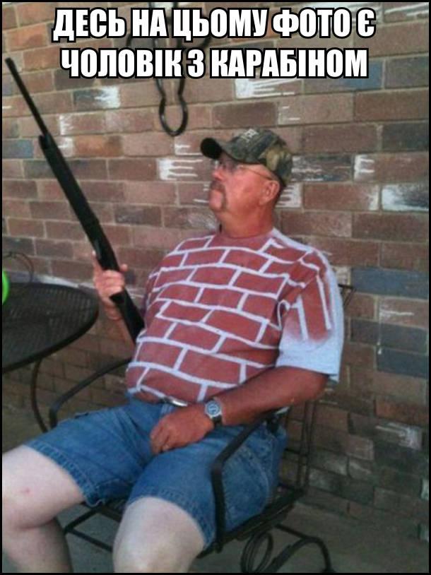 Десь на цьому фото є чоловік з карабіном. На фоні цегляної стіни сидить чоловік в футболці на якій намальовані цеглини