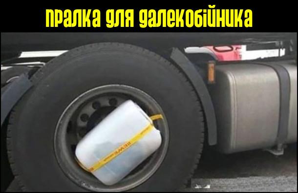 Пралка для далекобійника. Ємність з білизною, водою і порошком прив'язана до колеса вантажівки