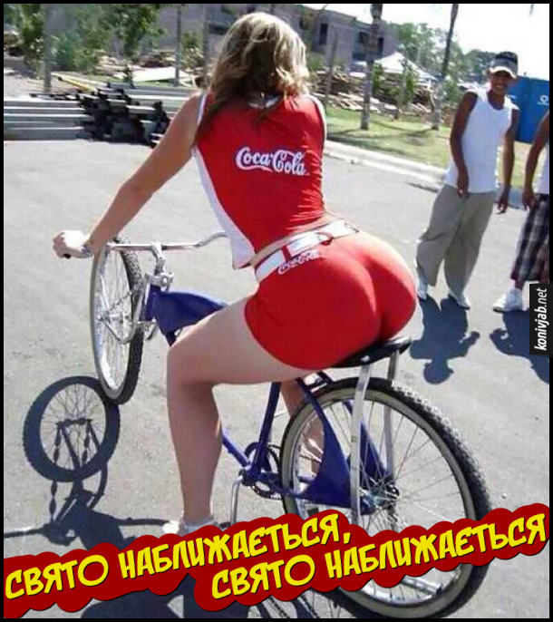 Новорічна реклама. Дівчина з великою дупою їде на велосипеді в в фірмовому костюмі Coca-Cola. Свято наближається, свято наближається