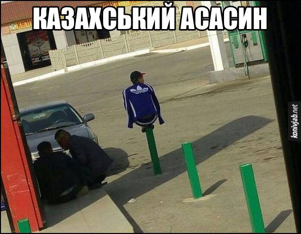 Прикол Казахстан. На заправці на залізному стовбчику сидить хлопець в спортивці adidas. Казахський асасин