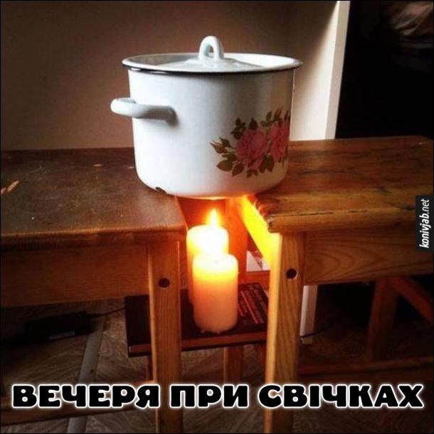 Прикол Вечеря при свічках. Між двома табуретками поставили каструлю, а знизу дві свічки, щоб розігріти її