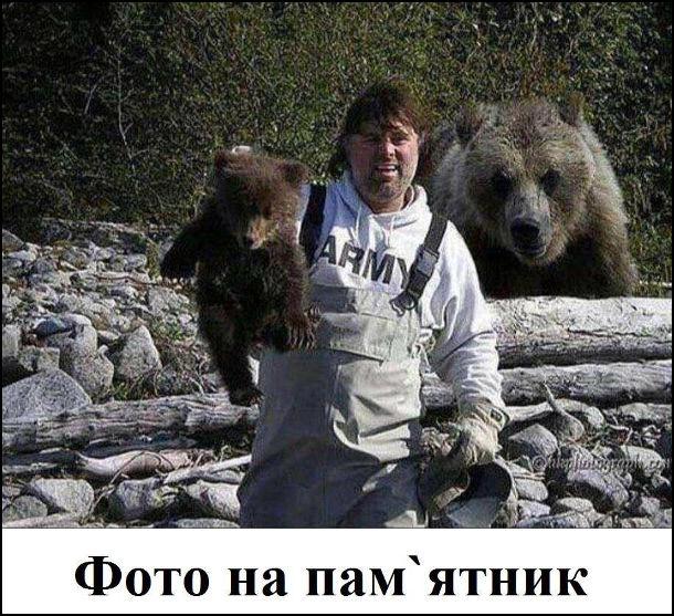 Прикол Чоловік і ведмежа. Чоловік робить фото з ведмежам, тримаючи його за шкірки, а в цей час до нього ззаду наближається ведмедиця (мати ведмежати). Судячи з усього це буде фото на пам'ятник