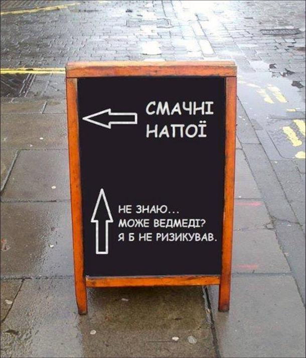 """Смішна рекламна дощечка. Одна стрілка показує до рекламованого закладу, підпис """"Смачні напої"""". Інша стрілка показує далі по тротуару, підпис """"Не знаю... Може ведмеді? Я б не ризикував."""""""