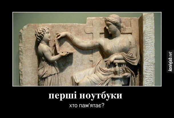Демотиватор. Перші ноутбуки. Хто пам'ятає? Антична скульптура, де одна людина тримає предмет, схожий на ноутбук, а інша людина ніби працює на ньому